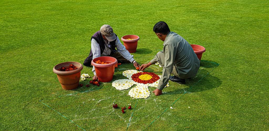 uomini fanno tappeti fioriti